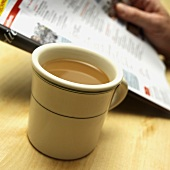 Cup of Coffee; Person Reading a Magazine