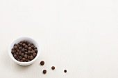 Allspice berries in a bowl and next to it
