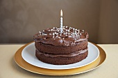 A chocolate cake decorated with silver balls and a candle