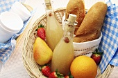 A picnic basket with ginger beer, fruit and bread