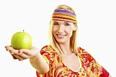 A young woman with a headband holding out a green apple