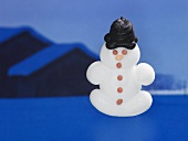A sugar snowman in front of a winter landscape
