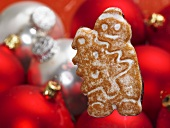 A Christmas biscuit with Christmas tree baubles in the background
