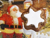 A cinnamon star with a Father Christmas figure in the background