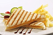 Toasted cheese sandwich with chips, balsamic vinegar and a salad garnish