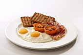 English breakfast (fried egg, bacon, wholemeal toast, tomatoes)