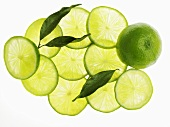 A whole lime, lime slice and lime leaves