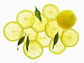 A whole lemon, lemon slices and leaves