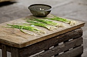 Spring onions lying on a rustic wooden table