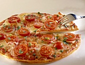 Pizza with tomato slices and cheese
