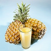 A glass of pineapple juice in front of two whole pineapples