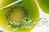 Slice of kiwi fruit and air bubbles in a glass