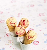 Scoops of vanilla and raspberry ice cream in cones