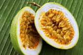 Halved passion fruit on palm leaf