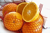 Oranges in opened net, one halved
