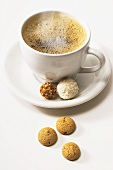 Steaming coffee cup with two chocolates and amarettini