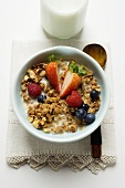 Crunchy muesli with berries and milk in cereal bowl