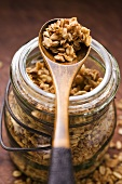 Crunchy muesli in a jar and on a wooden spoon