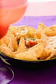 Tortilla chips and salsa in a bowl, cocktail beside it