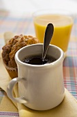 A mug of coffee, muffin and orange juice