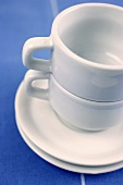 Two empty espresso cups with saucers in a pile