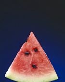 Slice of Watermelon with Seeds on a Blue Background
