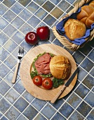 Roast Beef Sandwich with Tomatoes on a Round Wooden Plate