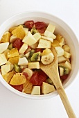 Bowl of Fruit Salad with Wooden Spoon; From Above
