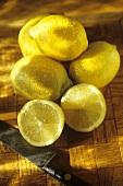 Whole Fresh Lemons with a Halved Lemon; Knife