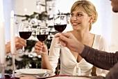 Junge Frau stösst mit zwei Menschen mit Wein an