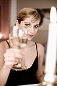 Junge Frau hält Weinglas zum anstossen