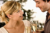 Man and woman clinking champagne glasses