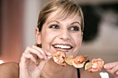 Young woman with shrimp kebab in her hand