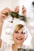 Junge Frau schmückt Weihnachtsbaum