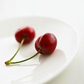 Two cherries on a plate