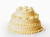 A three-tiered cream cake on white background