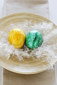 Two coloured Easter eggs with feather in wooden bowl