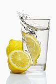 Eine Zitronenspalte fällt in ein Glas Wasser