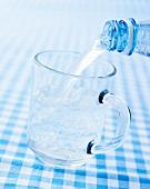 Mineralwasser in ein Glas gießen