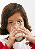 Kleines Mädchen trinkt ein Glas Milch
