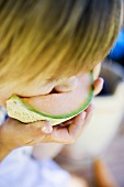 Small child biting into a slice of melon