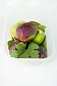 Several figs with leaf in plastic punnet