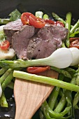 Roast beef with asparagus, tomatoes and spring onions