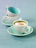 A cup of cappuccino and two empty cups