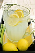 Lemonade in a glass jug with slices of lemon and ice