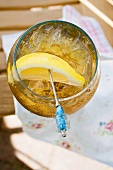 Rum and tonic with ice cubes and lemon wedge