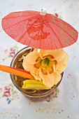 Cuba Libre with cocktail umbrella and amaryllis flower