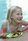Kleines Mädchen mit frischen Früchten am Pool