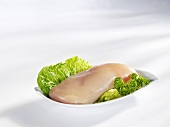 Raw chicken breast fillet on lettuce leaf