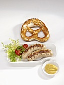 Two fried sausages with mustard and pretzel